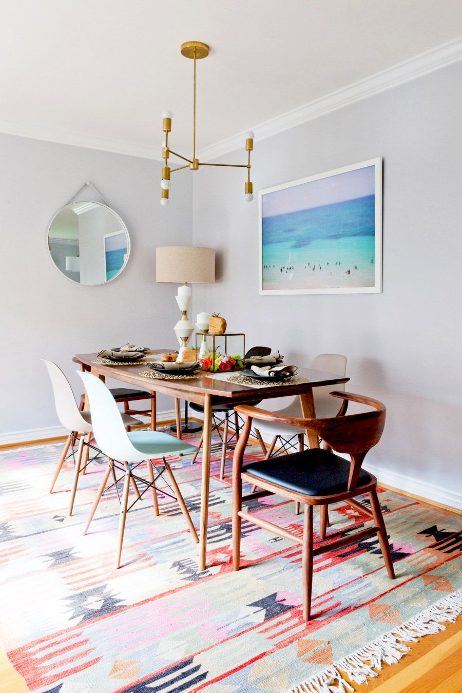 Bright And Vibrant Dining Space With Beautiful Beach Art And Round Hanging  Mirrow
