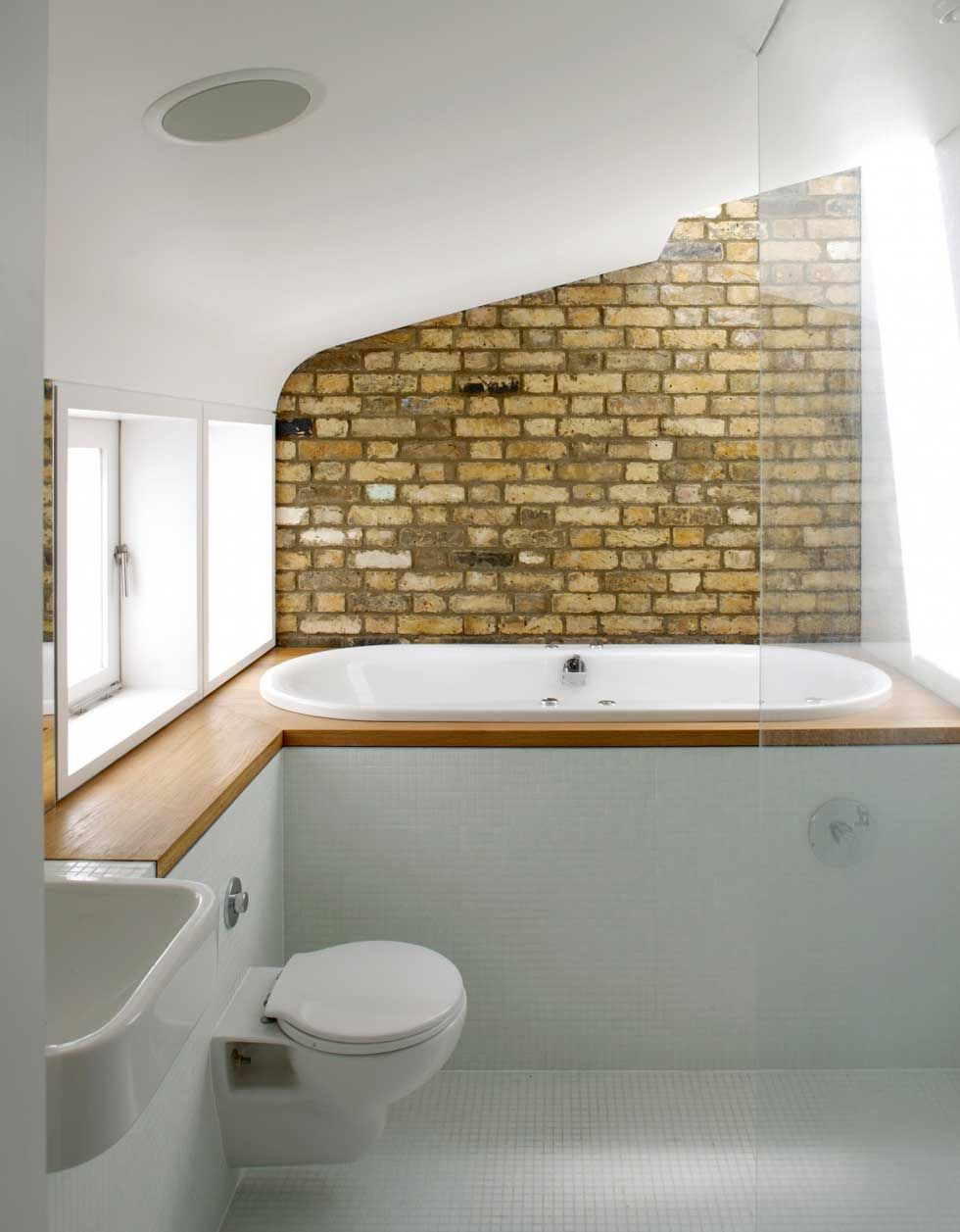 The bathroom with exposed brick behind the raised bathtub for Kitchen ideas victorian terrace