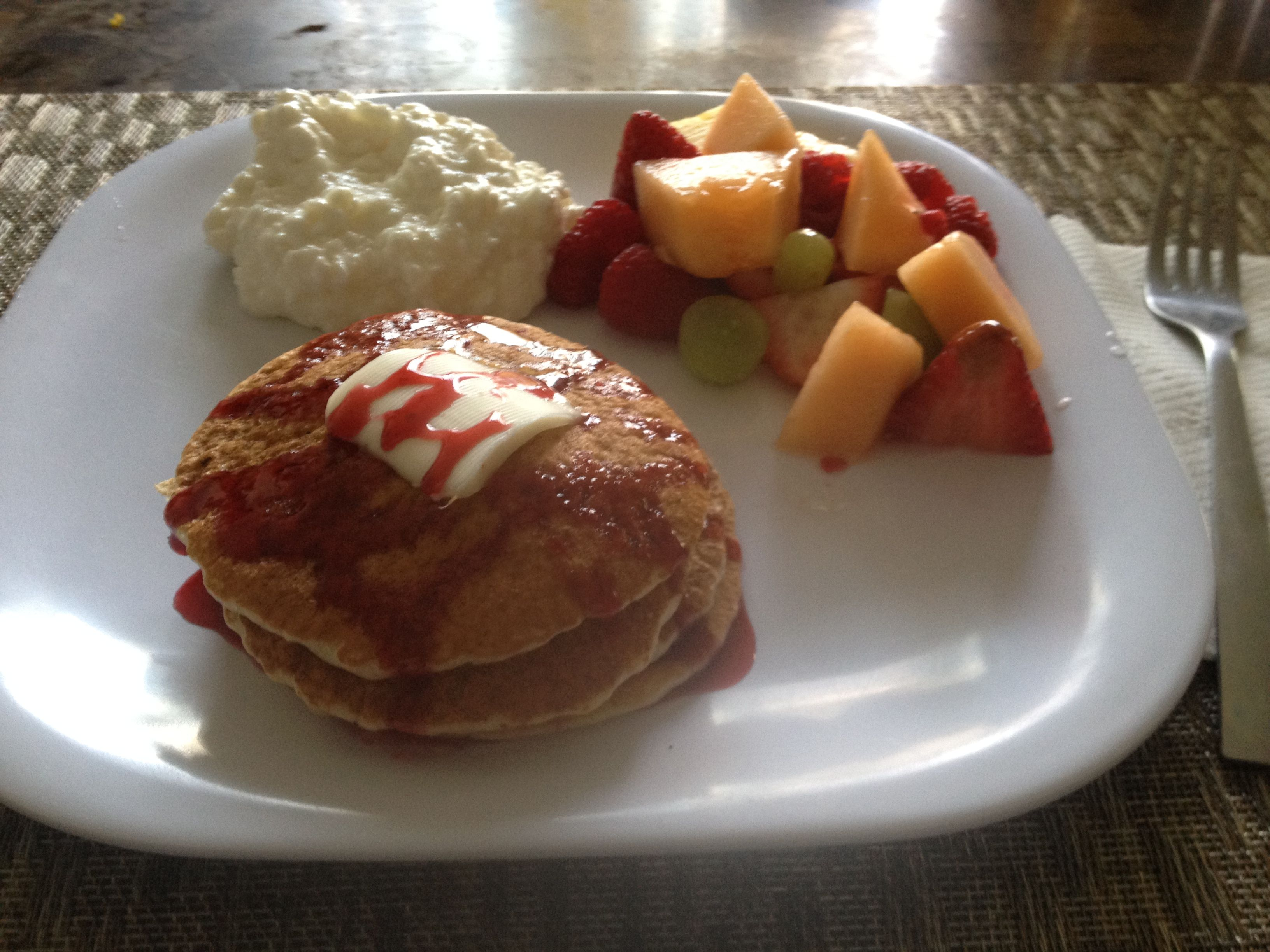 Whole wheat flapjacks with raspberry syrup, cottage cheese and fruit salad.