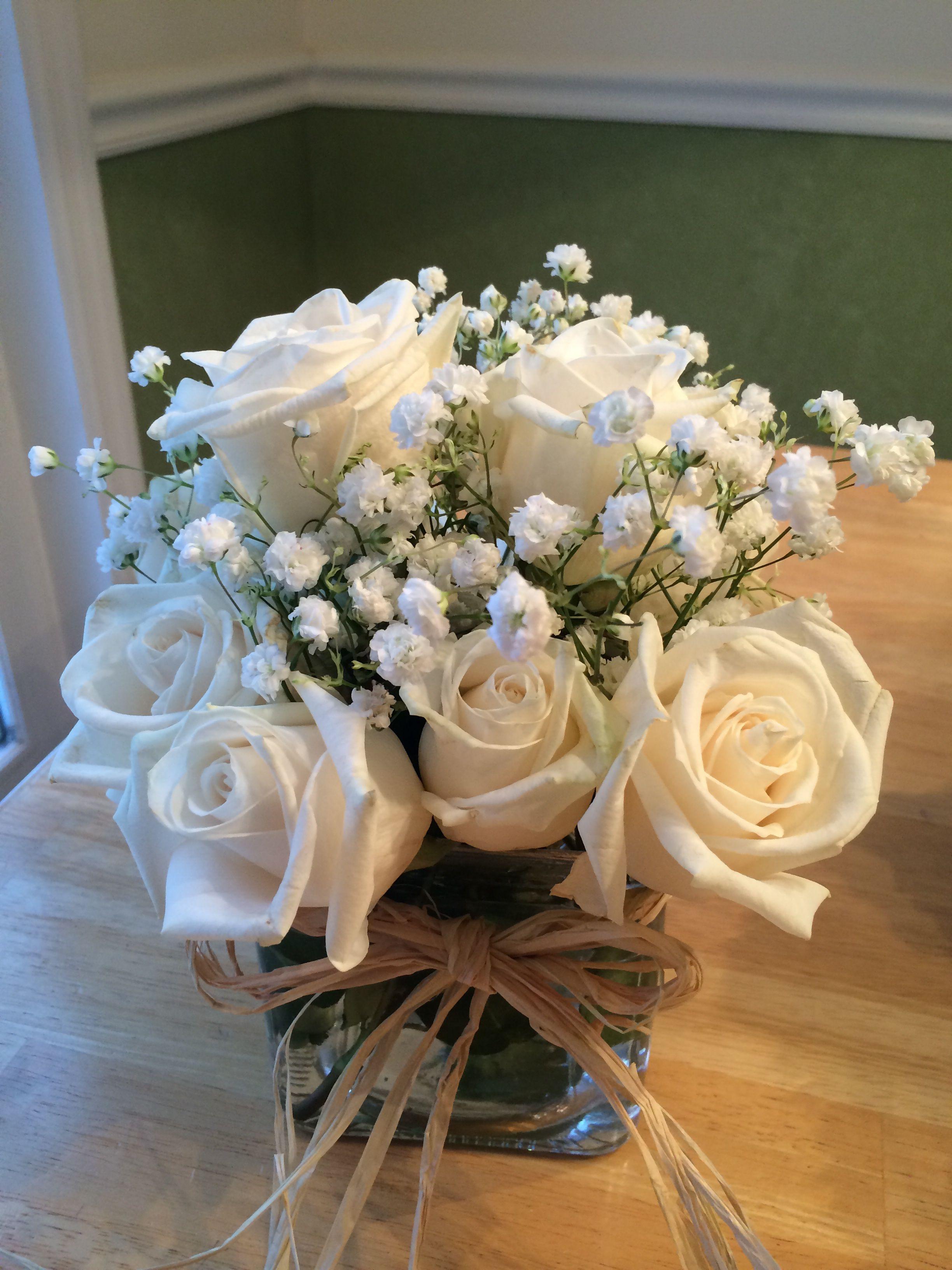 A dozen roses in a small 4x4x4 vase tie raffia around