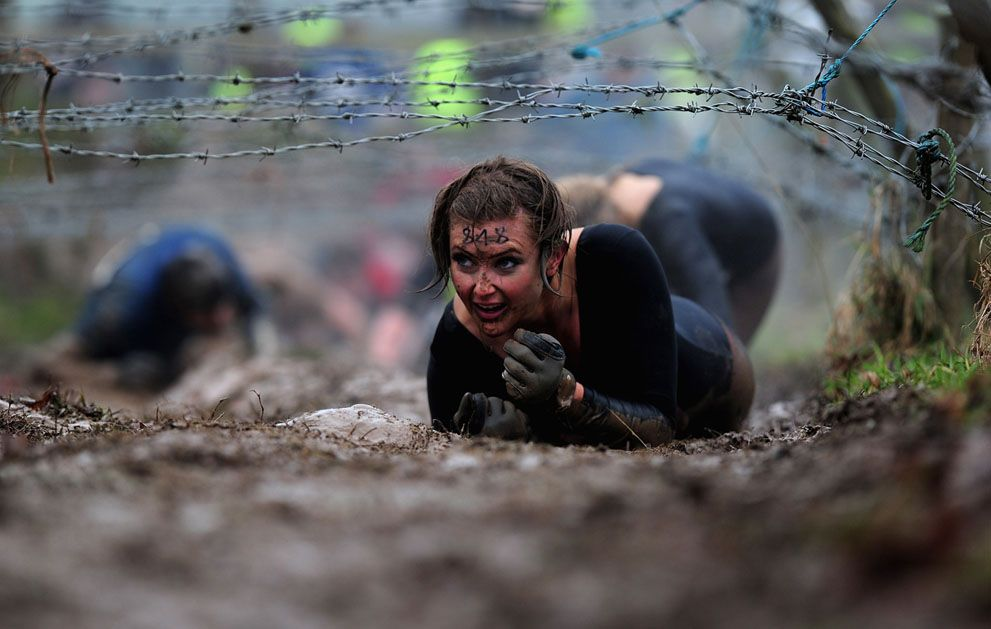 A woman crawls under barbed wire during the Tough Guy Challenge 2012 Perton, England.