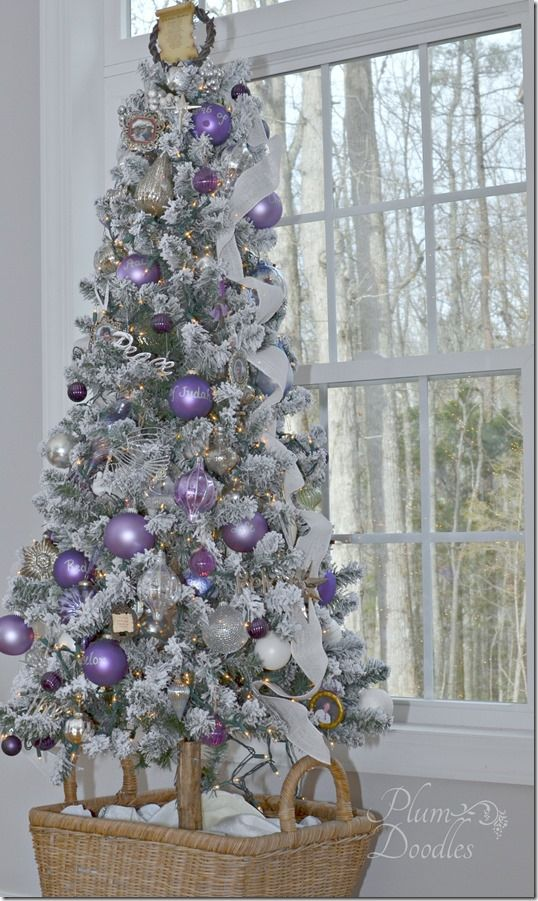Purple, lavender, white, and silver decorations on a flocked tree. In a  basket on wheels! PlumDoodles.com - A Purple, White, And Silver Themed Christmas Tree