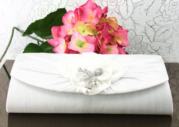 """Wedding Clutch Wedding Purse White Satin by goddessdesignsgems, $68.00 """"Absolutely Gorgeous"""" classic elegance, this clutch features a shimmering white satin shell with a beautiful bow applique in the center embellished with a """"double drop pearl"""" crystal brooch for a very stunning look. Magnetic snap closure under the front flap, easily secures items inside."""