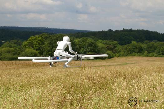 A white plastic robot zooms hoverbike over English countryside,grains blowing beneath bike's four fans.Robot's 3-D printed body lightweight,& where face would be there's a GoPro camera,filming flight.Isn't scene from dystopian science fiction movie;Bike less than four feet long,& combined robot & bike weighs maximum of 15.4 pounds.Created by Malloy Aeronautics,Drone 3 hoverbike 1/3rd scale model of version ultimately intended for human pilots & passengers.