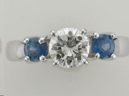 three stone ring with round diamond center and natural blue sapphire accents set in 14kt white gold