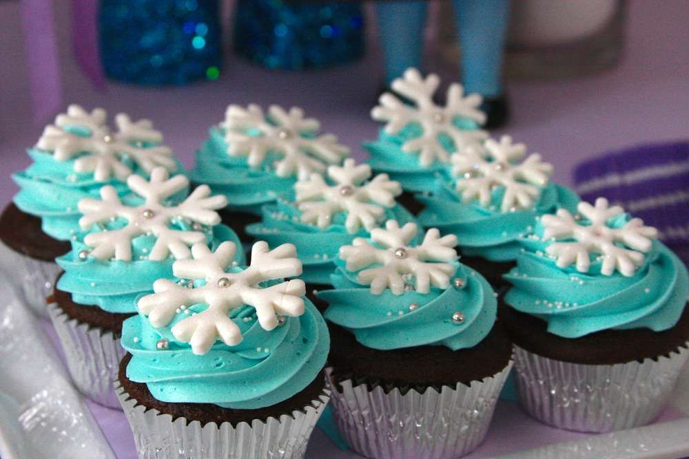 snowflake topped cupcakes at a frozen girl birthday party see more party planning ideas at