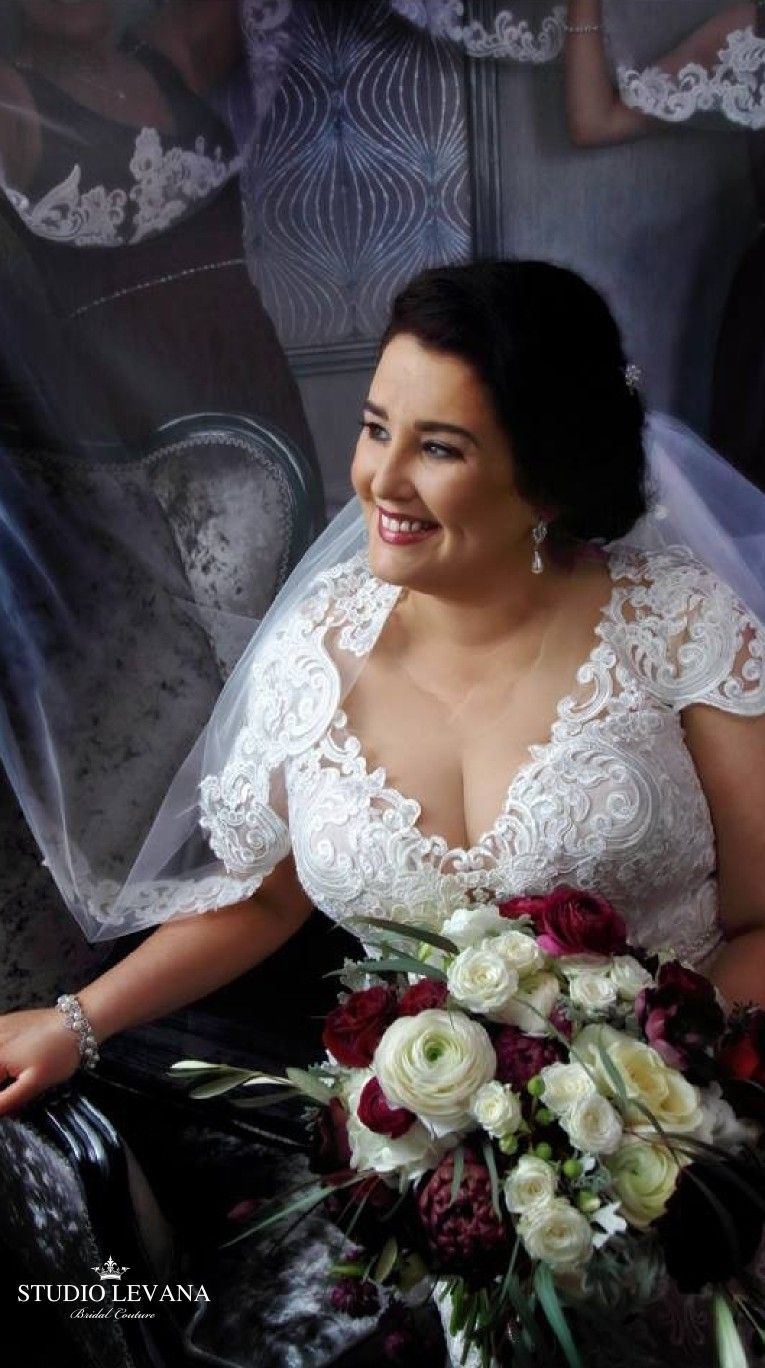 Real bride in a plus size lace wedding gown with short sleeves from