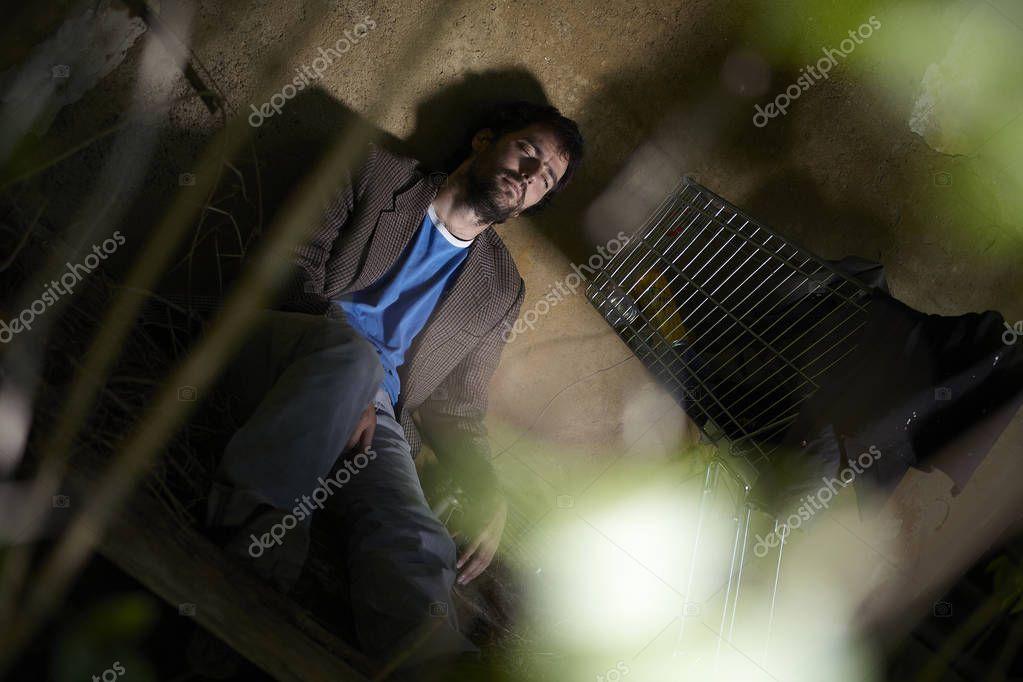 Beggar man sleeping while lying floor ruined house stock