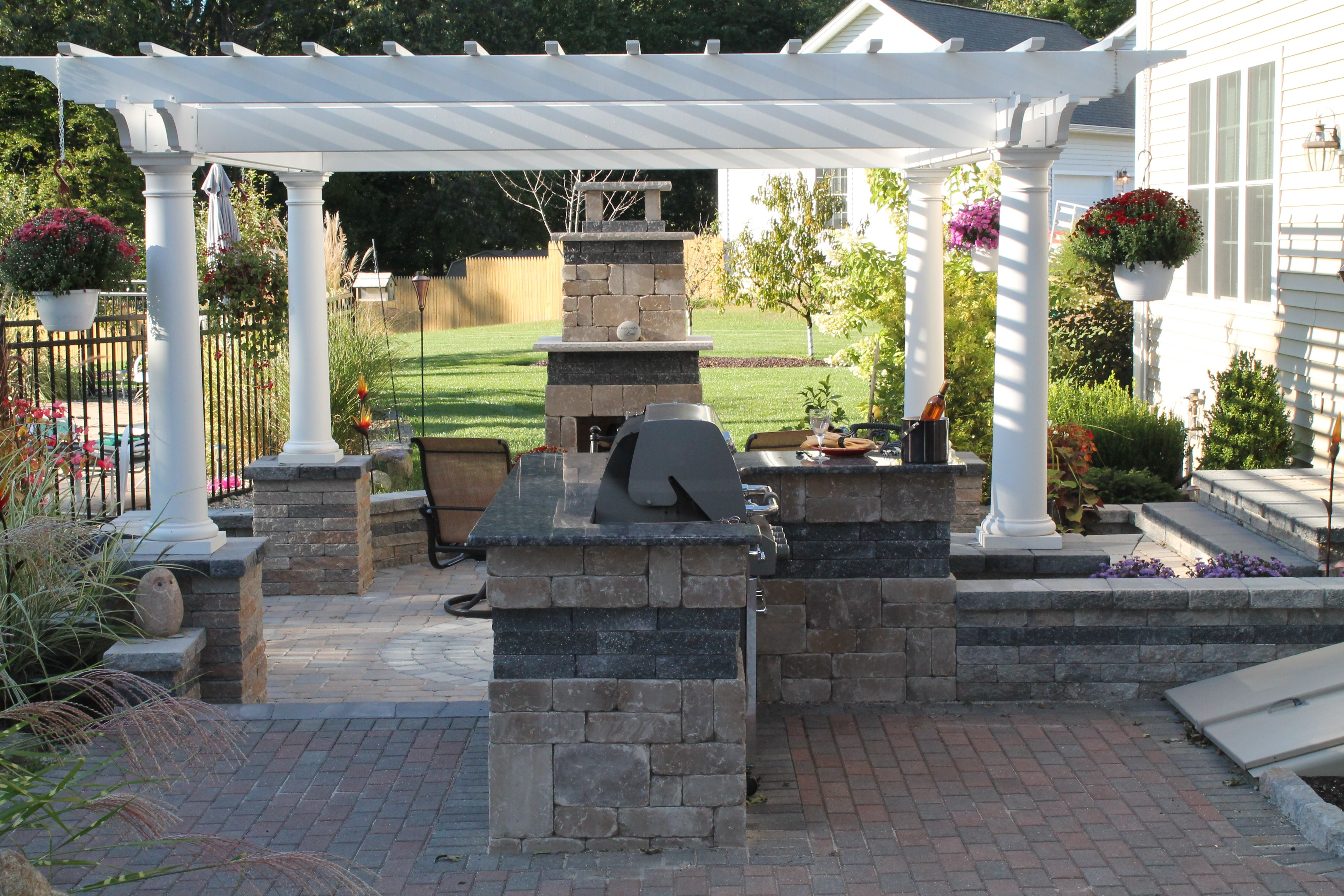 A Pergola Built On Columns Frames This Outdoor Fireplace With Outdoor Kitchen On A Multi Level Paver Patio By Bahler Brothers Pergola Patio Patio Design