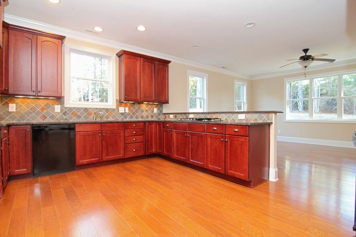 Peninsula kitchen with red tone cabinets. Black granite. Black ...