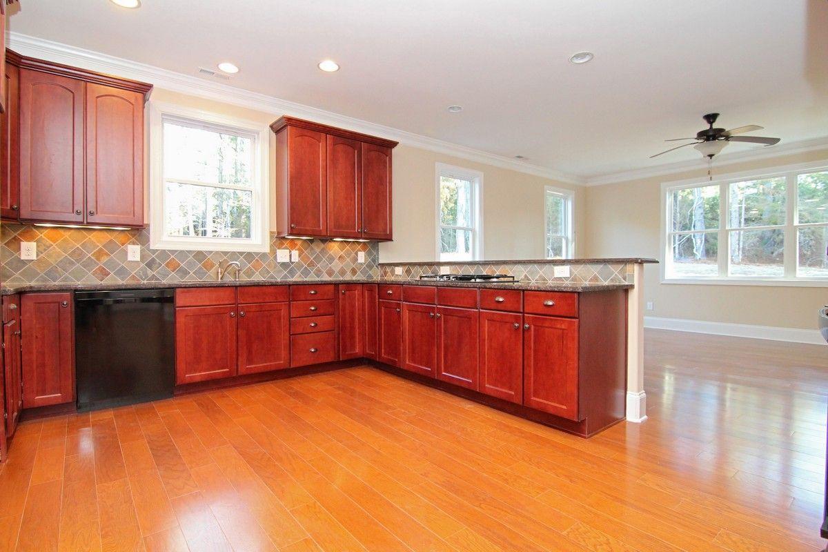 peninsula kitchen with red tone cabinets. black granite. black