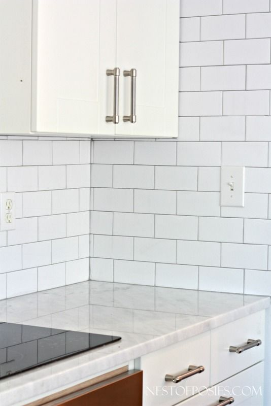 Our all white kitchen gets subway tile backsplash installation the DIY way.  Ideas and tips on subway tile backsplash installation for your own home.