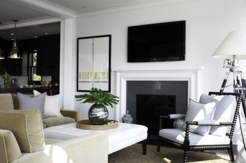 love this room:  black + white palette w/perfect shade of cream sectional┃ West Indies arm chair┃Restoration Hardware floor lamp┃silver accents┃simple + clean fireplace (no mantel)┃would just eliminate the t.v.