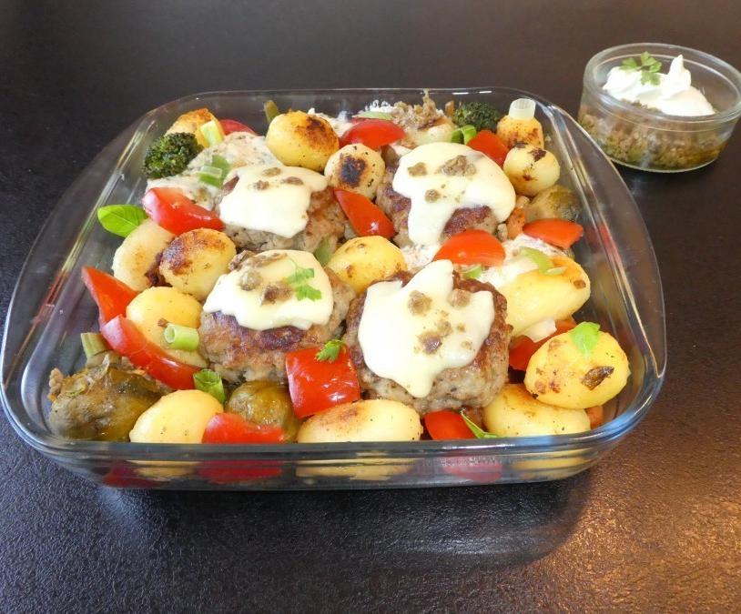 Mit Käse überbackene Pesto-Frikadellen im Gemüsebett - Rezept