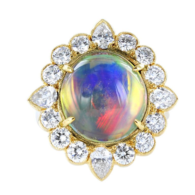Jelly Opal and Diamond Ring. 18 karat yellow gold cluster ring consisting of 1 oval shaped cabochon jelly opal weighing 6.32 carats, the center stone is set with 2.03 carats of round brilliant cut and pear shape diamond diamonds. 1stdibs.com.