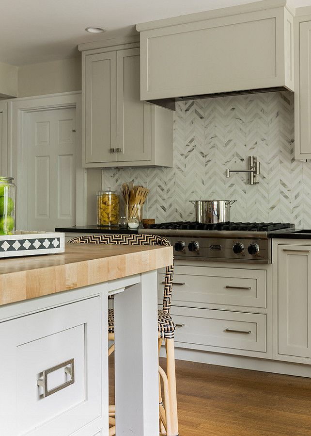 Gorgeous Kitchen With Pale Gray Cabinetry Accented With Nickel Hardware,  Black Perimeter Countertops And A Marble Herringbone Tiled Backsplash.