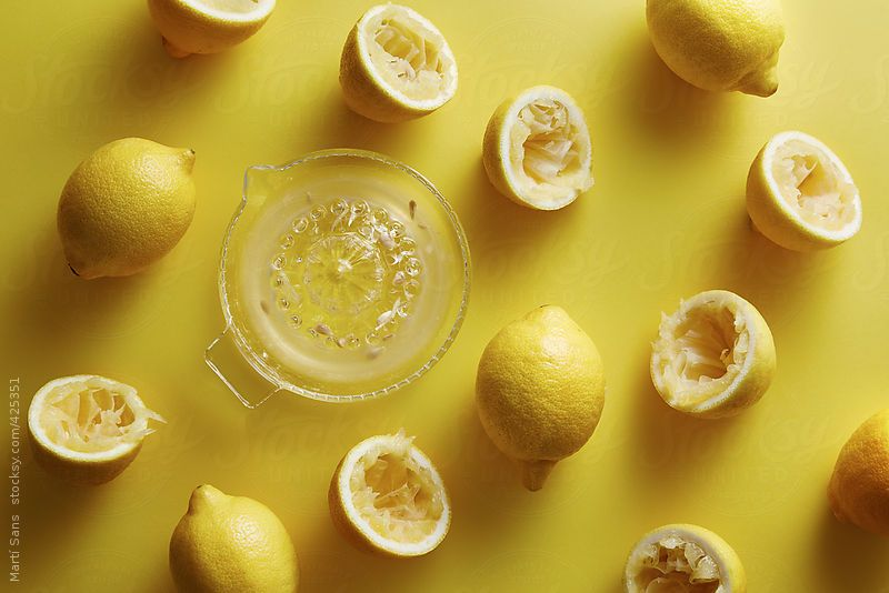 Overhead shot of squeezed lemons on yellow background
