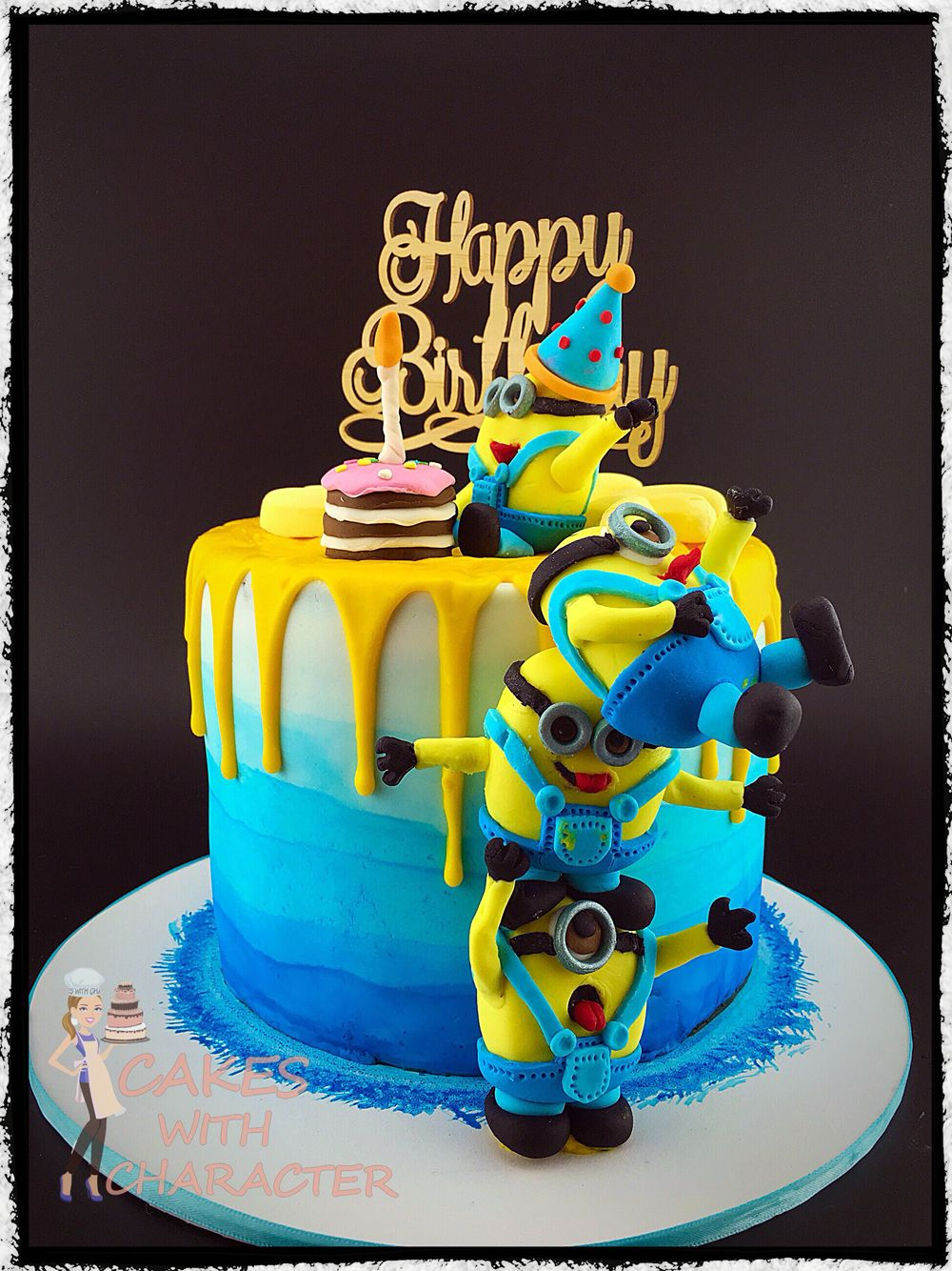Tower of fondant minions on ombre blue cake with yellow chocolate