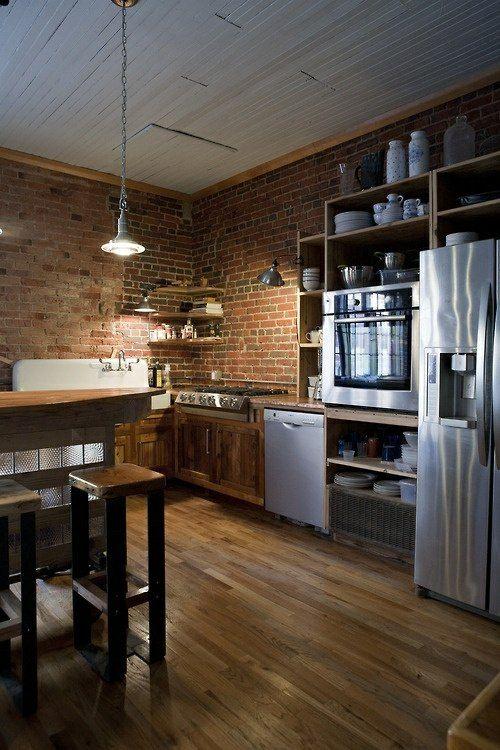 un sol et un plafond en bois et des murs en brique dans une cuisine simple