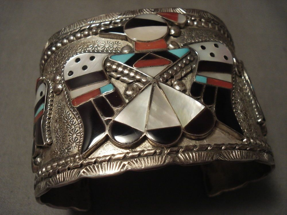 "This hand wrought very wide silver cuff bracelet contains three huge inlaid thunderbirds with the largest measuring around 1-5/8"" X 2"". The inlay consists of natural turquoise, corals, mother of pearl, and onyx. 