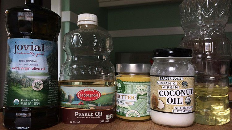 Different brands and types of cooking oil such as coconut oil, peanut oil and vegetable oil lined up side-by-side on a countertop
