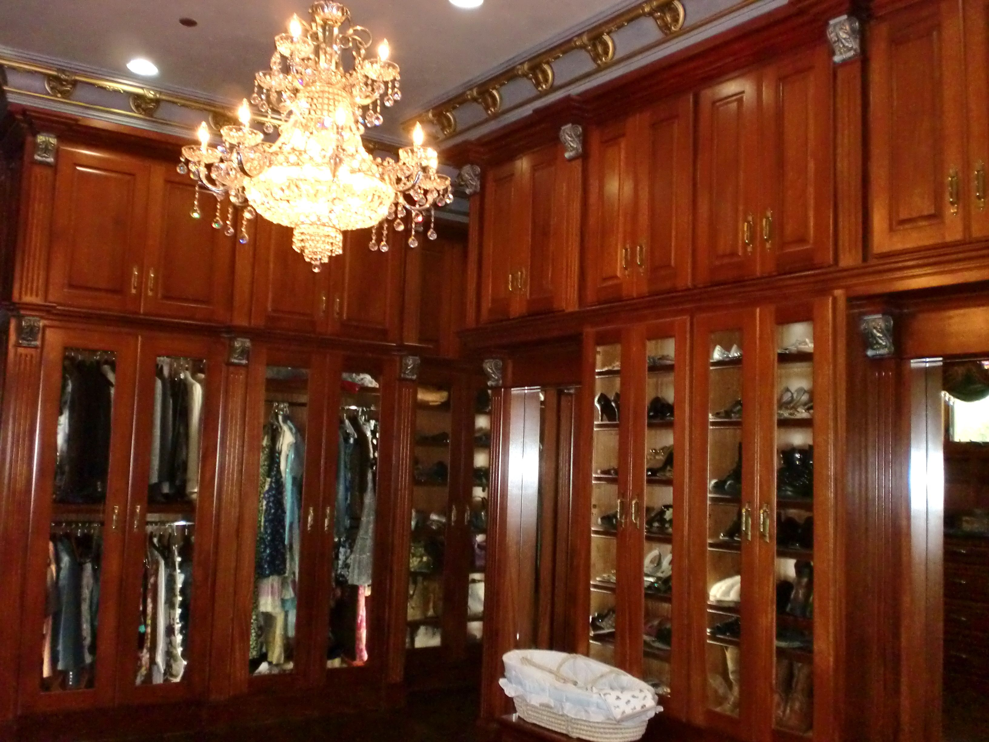 Master closet with built in cabinets, glass doors with LED ...