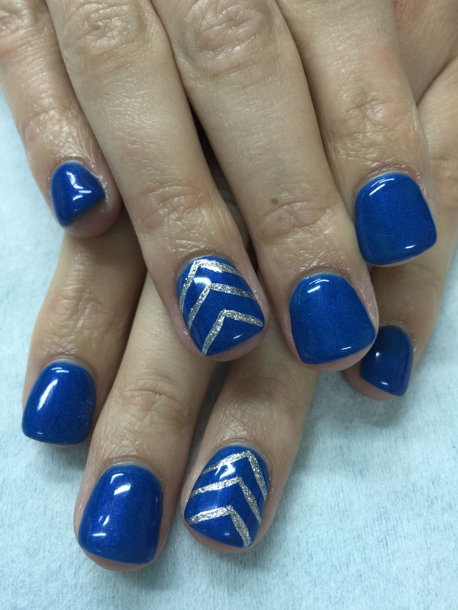 Royal blue glow in the dark gel nails accented with silver glitter ...