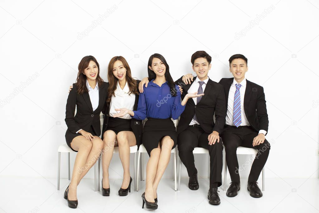 Portrait Of Asian Business People Sitting On The Chairs In A Row