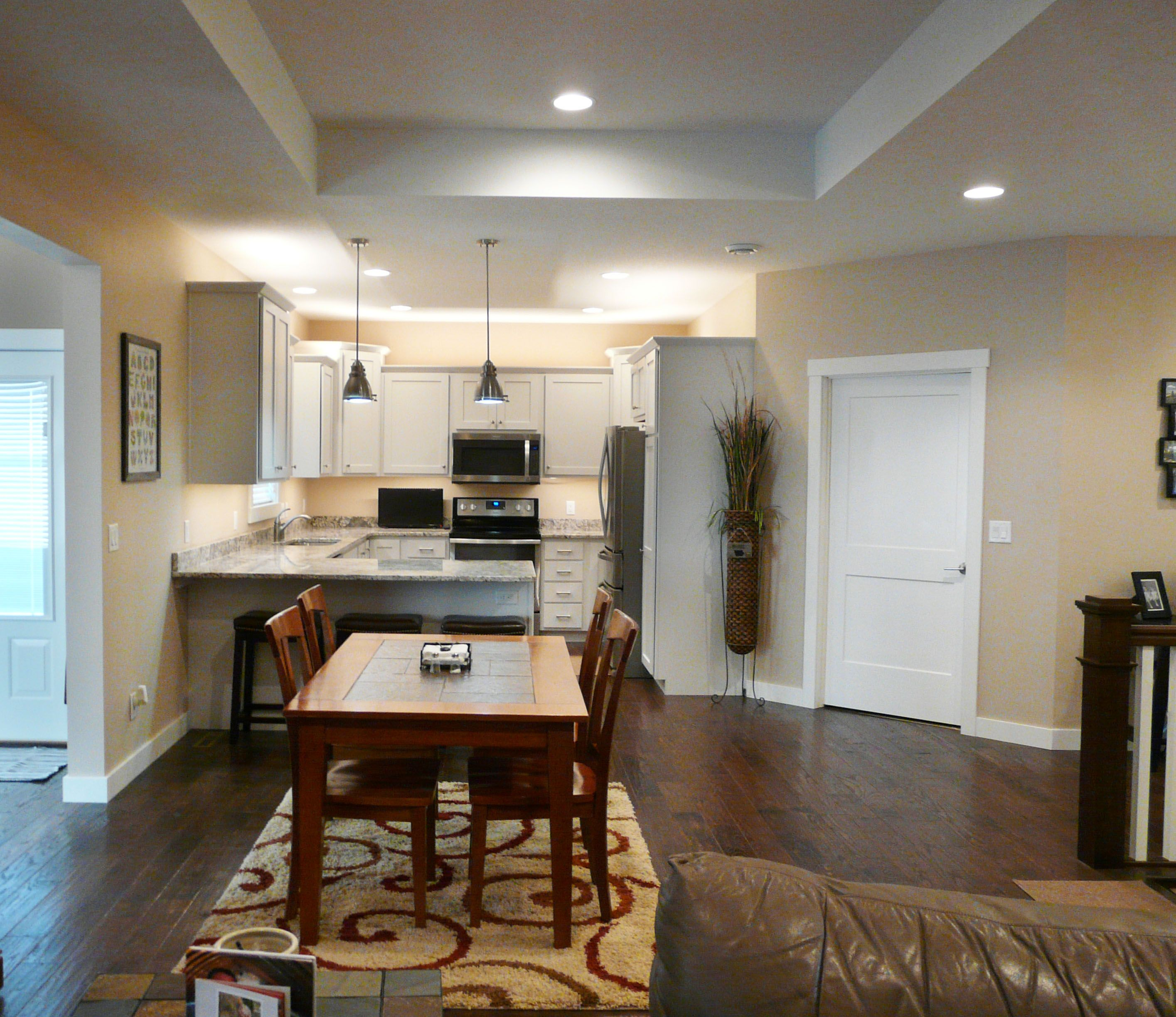 Open dining room into kitchen. White cabinets and hard ...