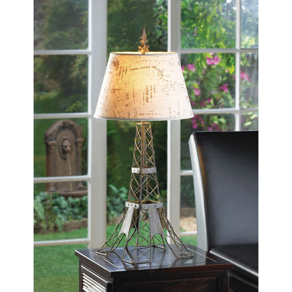 The metal wire frame mimics Paris most famous landmark, the Eiffel Tower, fashioned in industrial-inspired metal with a vintage patina. The travel-stamped shade and French flourish on top make this la