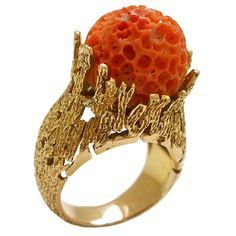 18k Gold and Coral Ring, Circa 1960 c1960 18k yellow gold and natural coral ring. The free-formed textured ring holds a natural coral carved into the shape ...