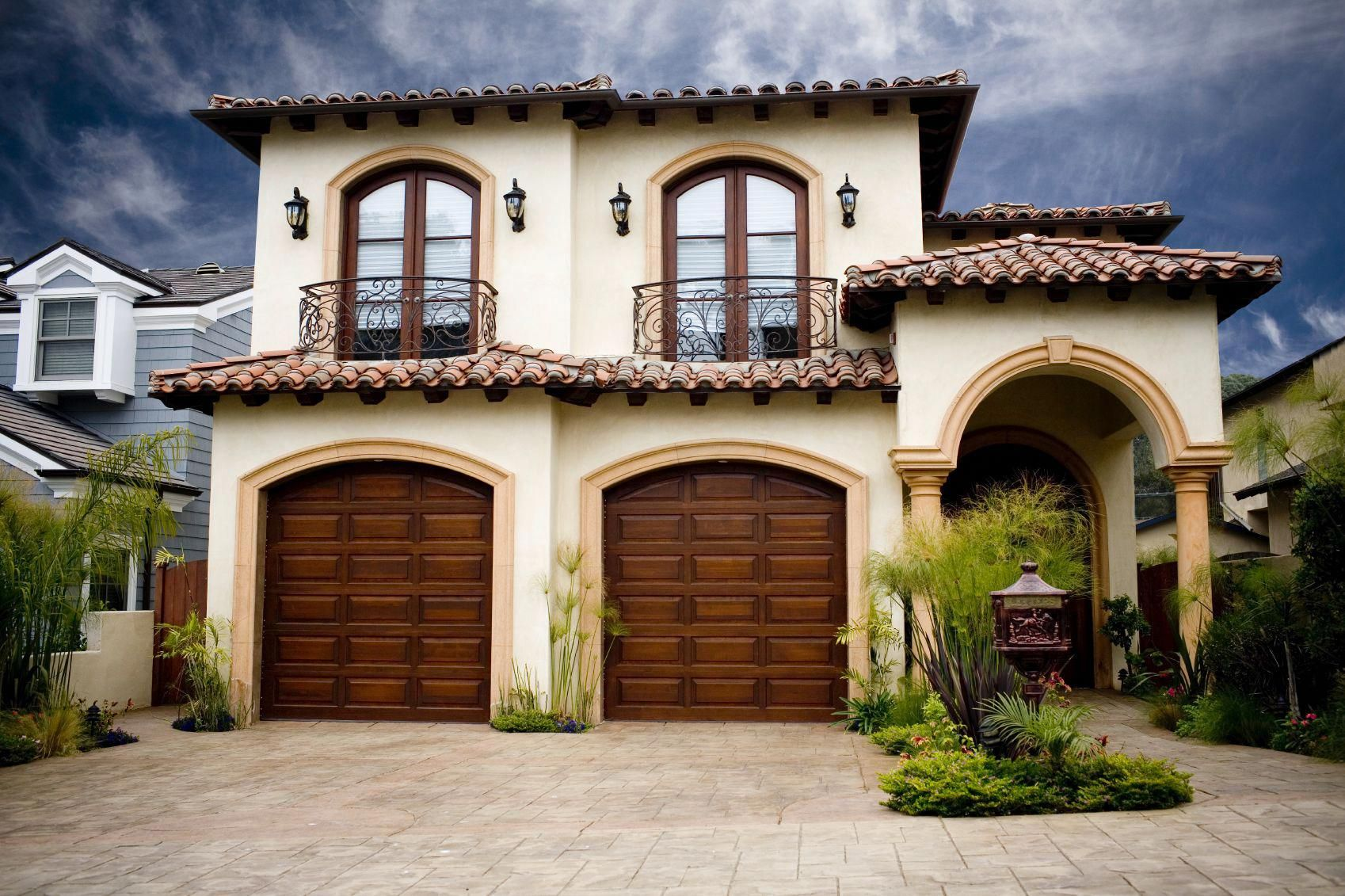 Double Single Car Garages Multicolored Tile Roof Covered Arched Entry Lights Anchoring The Window Spanish Style Homes Garage Doors Garage Door Spring Repair