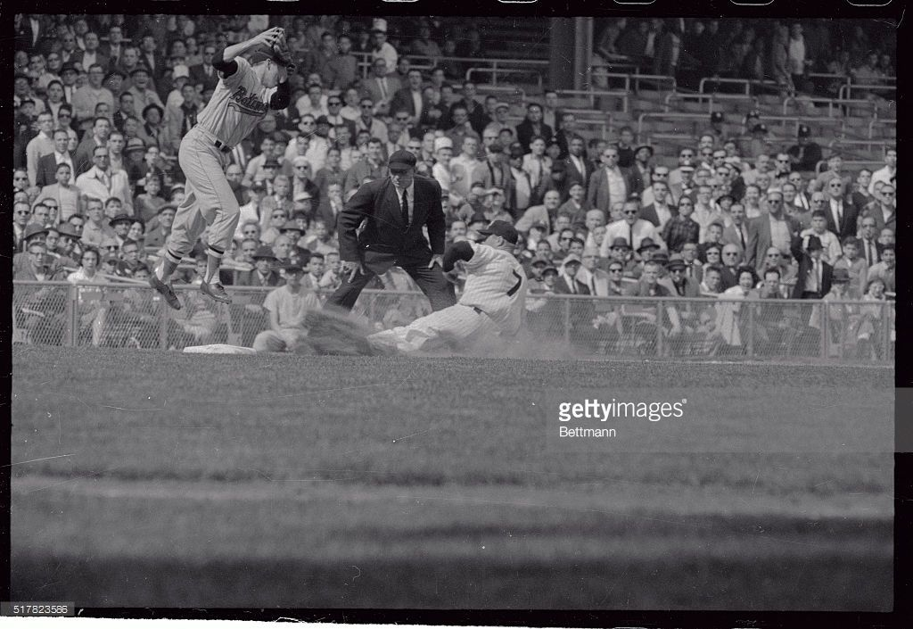 Baltimore's Brooks Robinson leaps high to get a throw from outfielder Jackie…