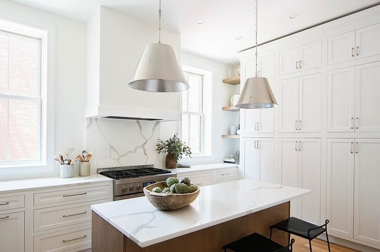 Floor-to-ceiling white shaker cabinets fitted with nickel pulls are positioned facing a brown stained island seating low back black metal counter stools at a statuary quartz countertop lit by two nickel pendants. #whiteshakercabinets