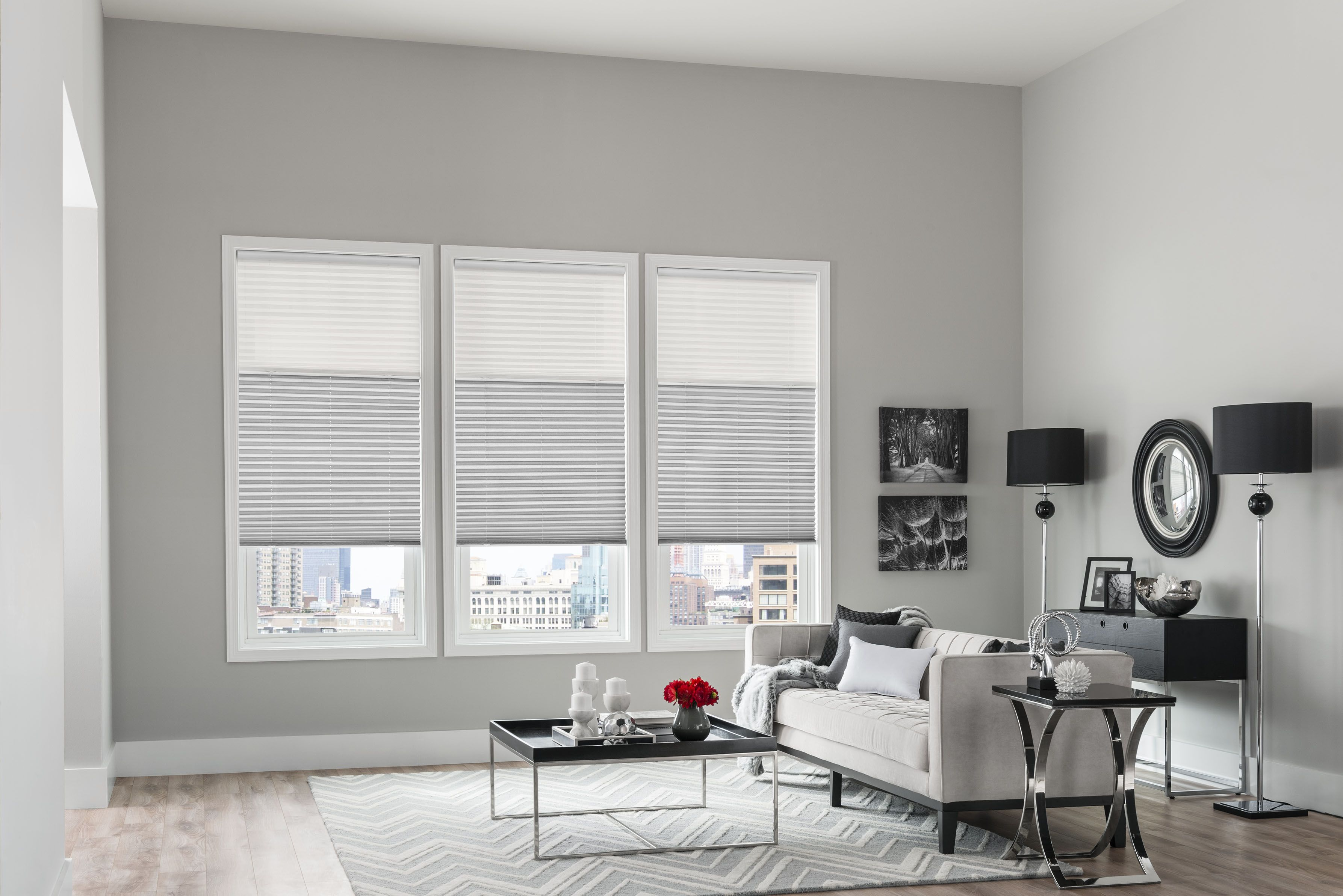 monochromatic gray cellular shades blend beautifully in this chic living room  accents of black