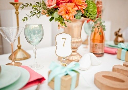 .A lovely table setting using the colors of seafoam/mint, saffron/orange, champagne golds and creams.