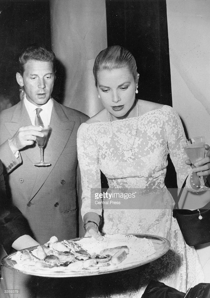French film star Jean Pierre Aumont (1909 - 2001) and American actress Grace Kelly (1928 - 1982) survey the hors-d'oeuvres at a reception in Cannes.