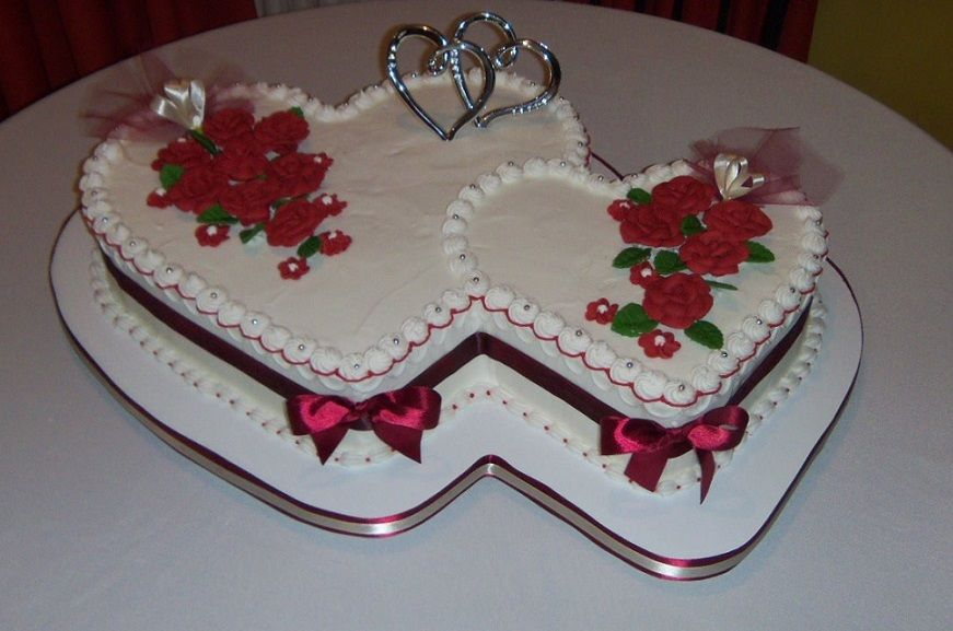 Twin Heart Shaped Wedding Cake Adorned With Red Roses And Ribbons