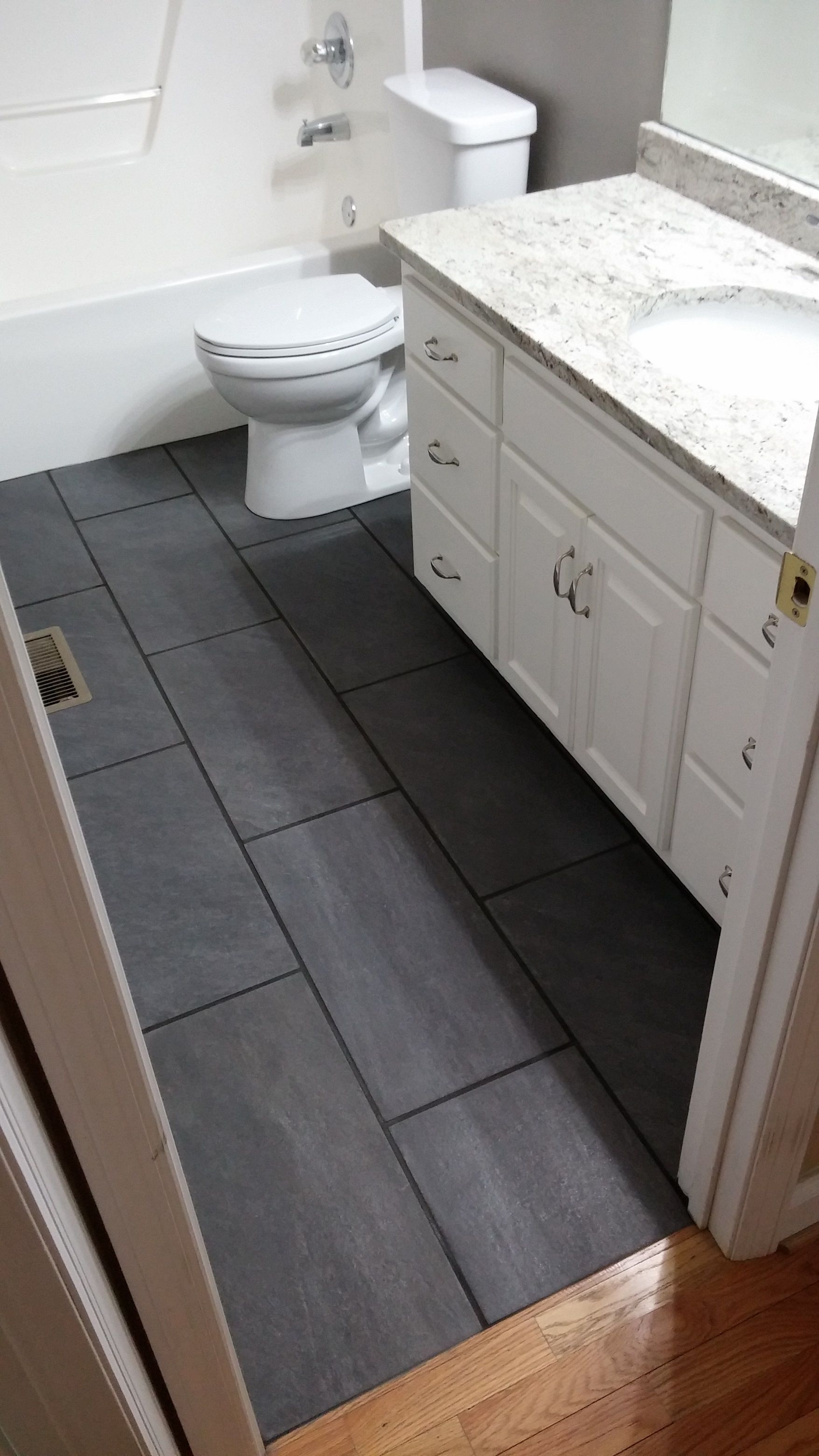12x24 Charcoal Ceramic Tile Installed In Guest Bathroom With New Delta Prelude Toilet Ceramic Tiles Tile Installation House Tiles