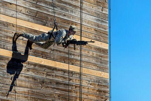 An Army Ranger carrying an M240 rappels down a wall as part of a demonstration during a Ranger school graduation on Fort Benning, Ga., Oct. 17, 2014.