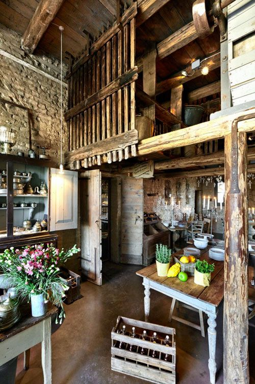 rustic Italian kitchen - I love everything about this. I love the rough edges. I love the cobbled wall. I love the open rafters and quasi-loft storage. I love the rough metal, the hewn look of the wood, and all the different shades of brown...  love love LOVE!  interior of cabinet is painted blue.  doors.  plank board table
