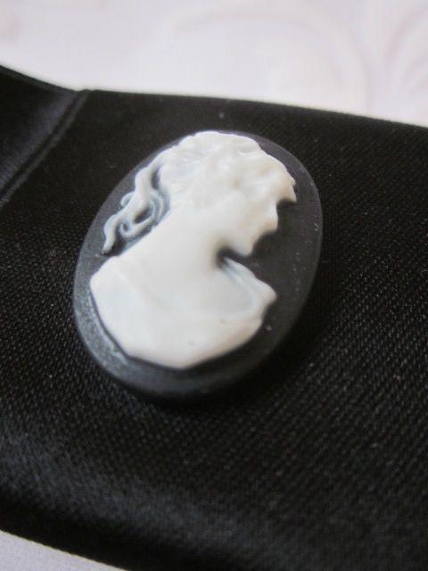 Brosche in Form einer Satinschleife mit einer Kamee in der Mitte