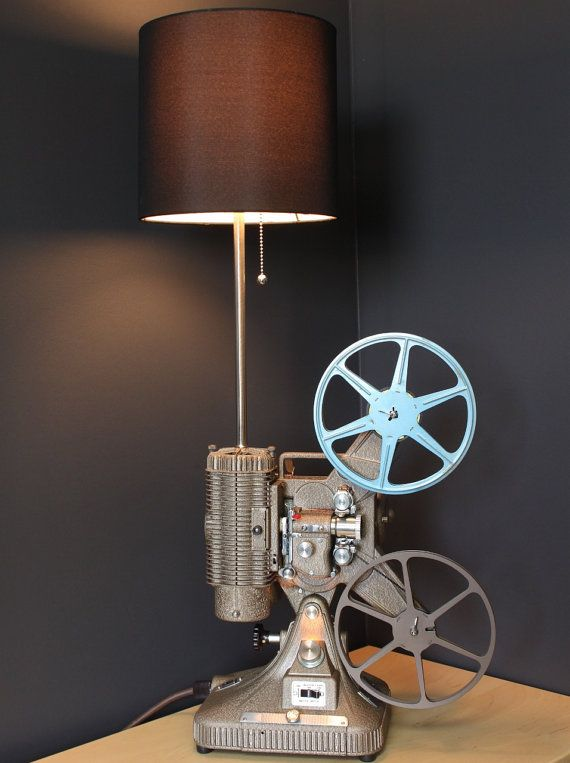 Old-fashioned Keystone Regal K-109 8MM projector converted into an exclusive table lamp.  Light and set-up light are controlled by the projectors Master Switch. Motor On turns the set-up light on and Light On the main light. The original projector light bulb has been removed and the motor has been disconnected. The lamp requires one 60-watt maximum standard bulb or 14 watt CFL bulb (not included).  The Keystone K-109, includes a Room Lamp Plug that is a nice feature for connecting your…