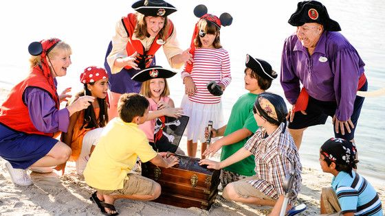Cast Members dressed as pirates engage a group of kids in a story as they dig into a treasure chest on a beach