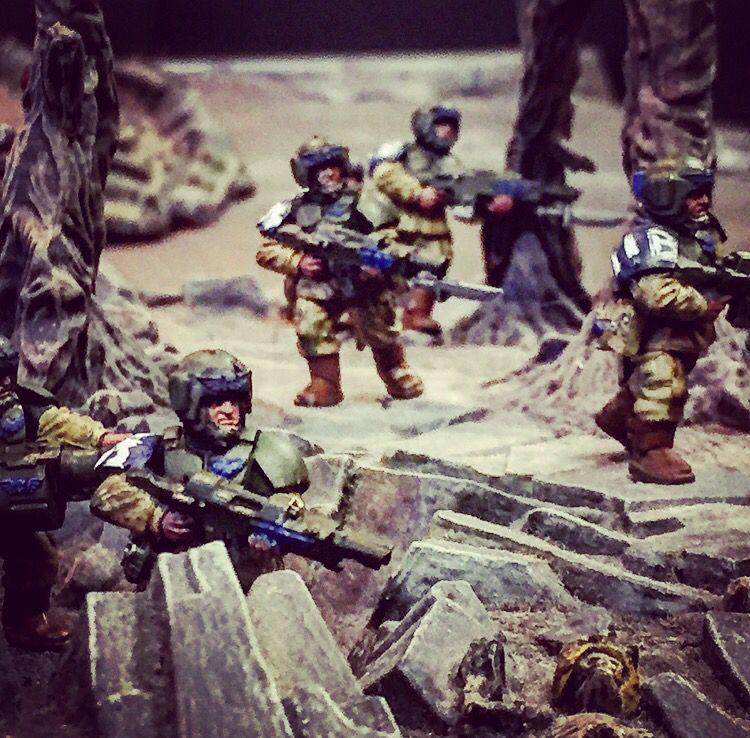 Astra militarium soldiers of the new 'Tigarian' regiment in 20th armoured brigade advancing on a fighting patrol. Notice the blue on one shoulder and on their eagles representing their regiment with white letters and numbers for their call signs