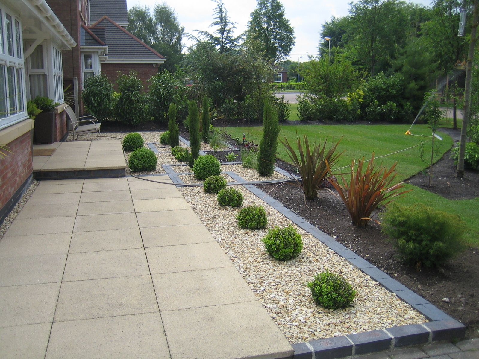 Marshalls saxon paving with golden gravel and blue black Outside rooms garden design