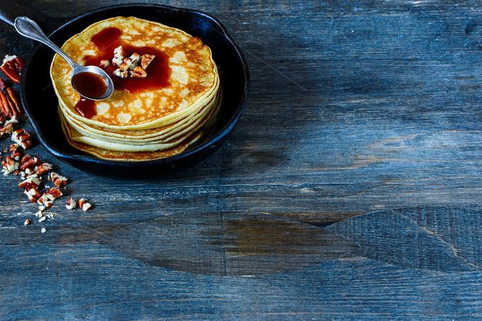 #Pancakes in pan  Tasty american pancakes with pecans and chocolate caramel sauce on vintage cast-iron frying pan over rustic background selective focus. Delicious dessert for breakfast