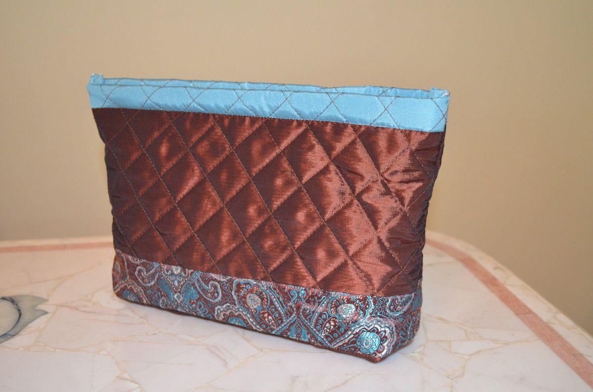 Necessaire, em Tafetá e Brocado de seda. <br>Mede 26 cm x 16 cm. <br>Possui um bolso interno. <br>Fechada com zíper