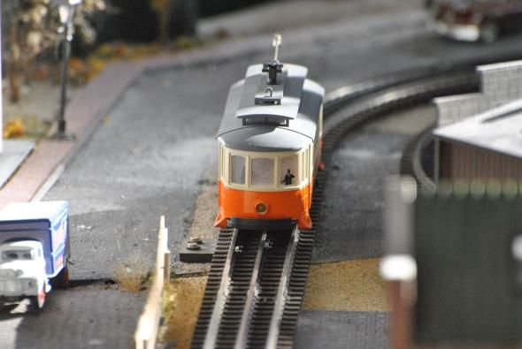 An MBTA Orange Line trolley travels down the city streets of the holiday train display at South Station. The display features several replic...