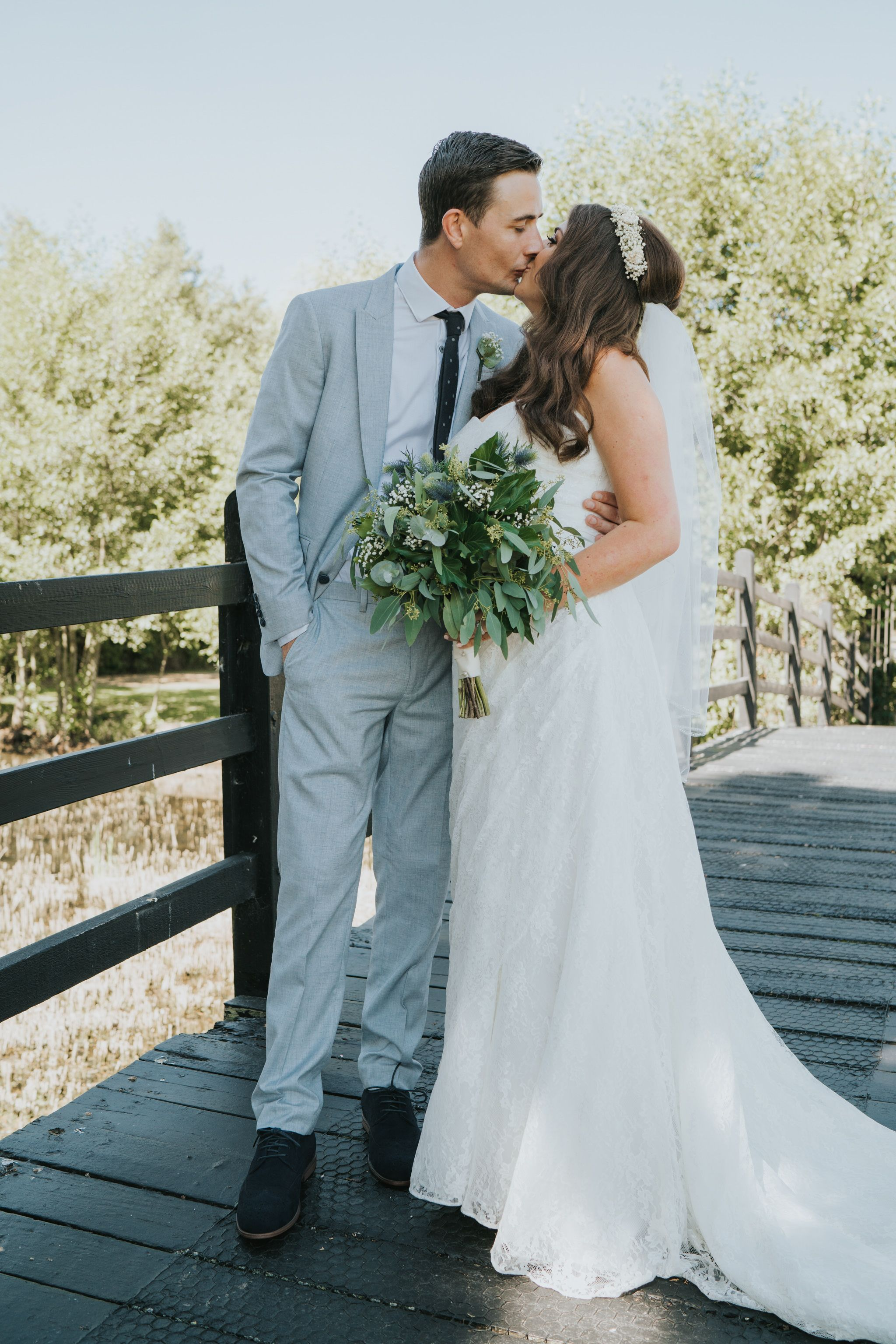 Cute portrait of bride and groom kissing on a bridge relaxed